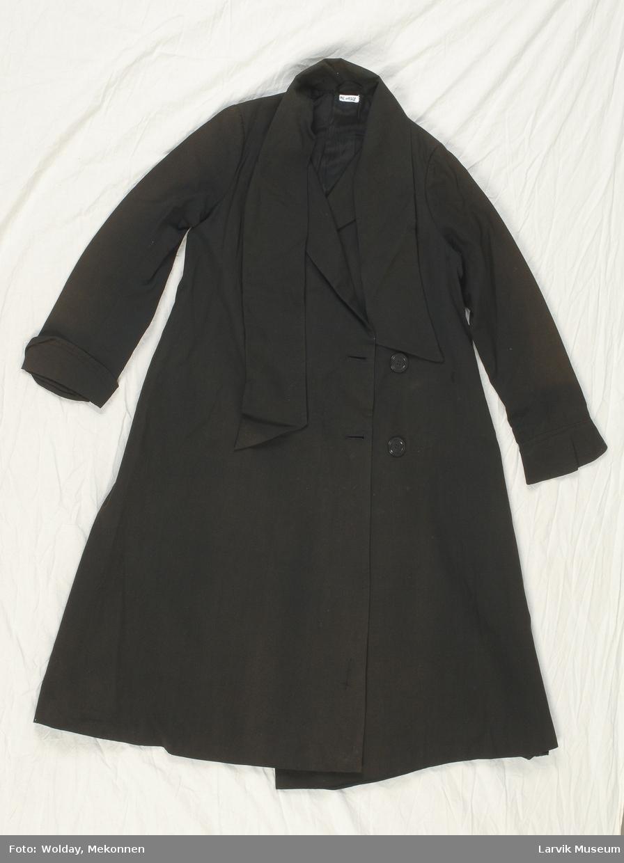 Form: Lang, lukkes med to knapper, krage går over i slips som kan knytes foran.