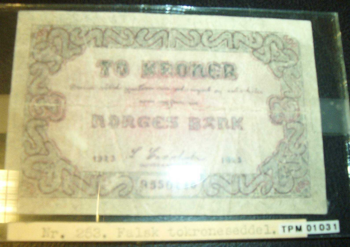Falsk tokroneseddel innlevert til Norges Banks avdeling i Trondheim den 20.03.1923. Seddelen var innkommet til Røeds lotterikontor i Dronningens gate samme dag uten at man der visste hvem som hadde levert den. I glassramme med målene: 8 X13 cm.