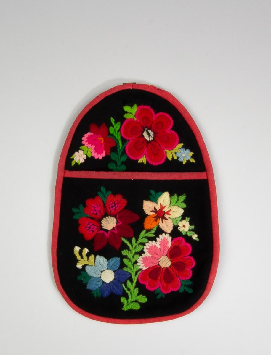 """Kjolsäck till dräkt för kvinna från Floda socken, Dalarna. Modell med avskuret framstycke. Tillverkad av svart ylletyg, kläde, med broderi, """"påsöm"""", av ullgarn i många färger: plattsöm, sticksöm, stjälksöm. Motiv: blommor och blad. Framstycket fodrat med rött fabriksvävt bomullstyg, satin. Alla kanter skodda med remsor av rött kläde. Bakstycke av svart bomullstyg, fabriksvävt i satin. Hake av metall, köpt."""