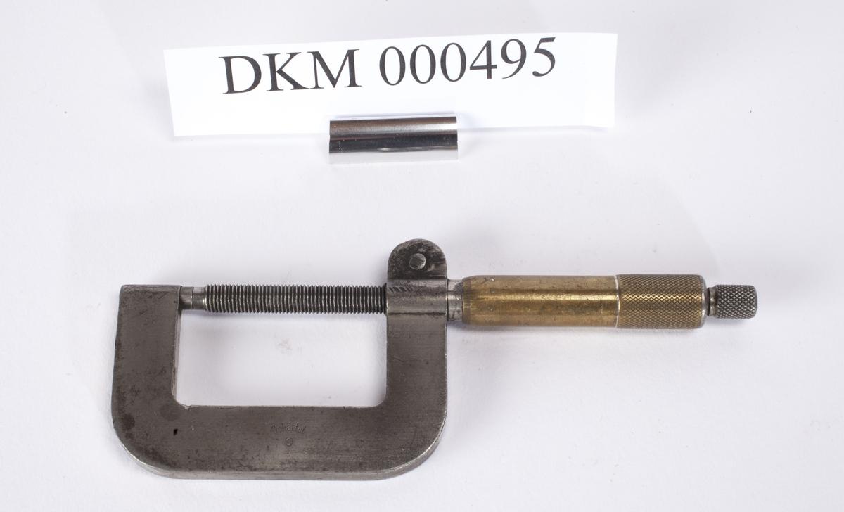 Håndtak med en lang skrue i enden. Toppen og enden av skruen er festet til en flat metalstang som er bøyd slik at den danner en firkant med skruen. Hele verktøyet for dermed fasong av en P. Måleskalaen går til 50 mm.