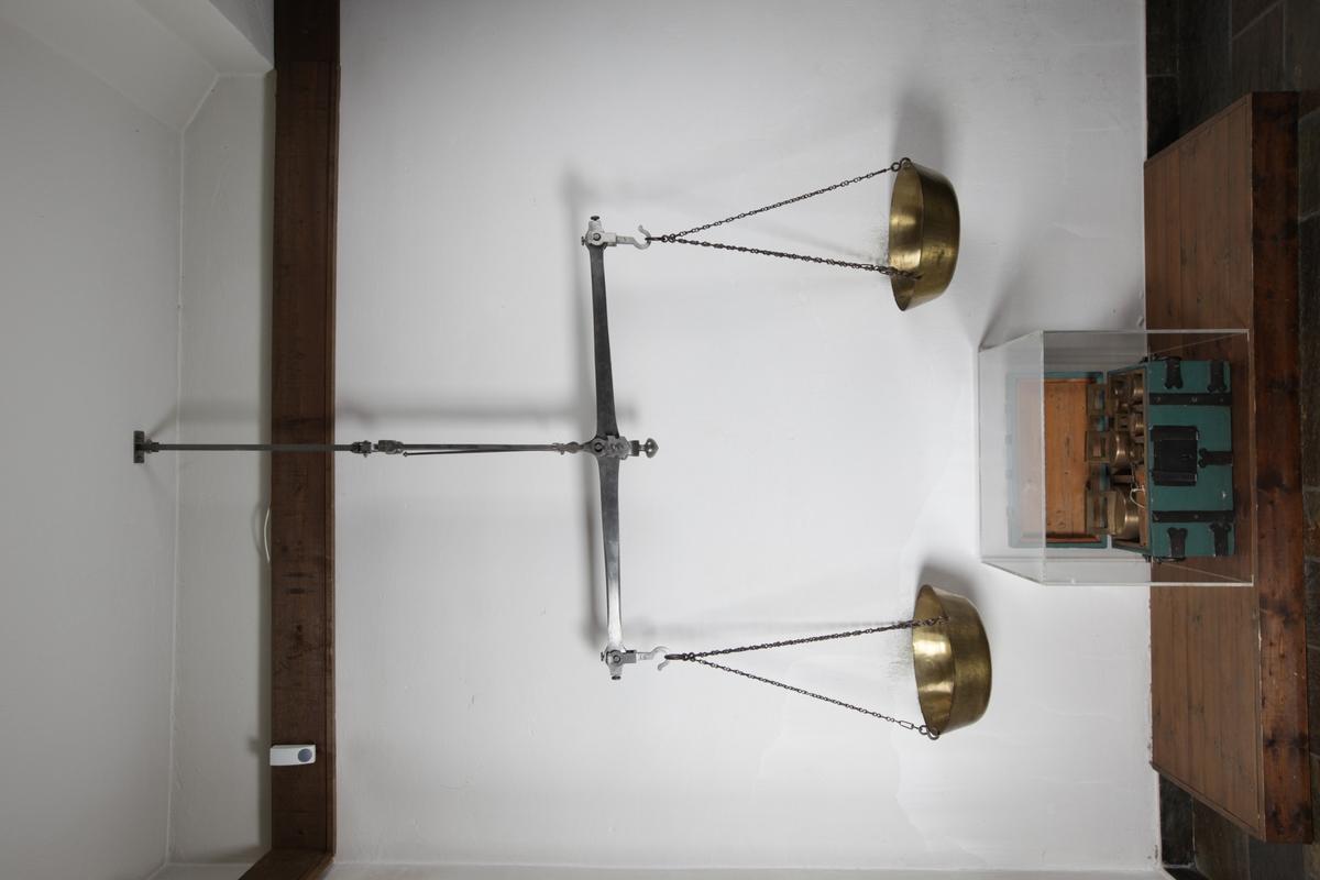 Vektarmen er festet i krok og kjetting som henger fra taket. Skålene er runde med kanter og henger fra vektarmen i kjettinger.