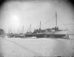 Seks seilskøyter på slipp i et vinterlandskap, trolig på And