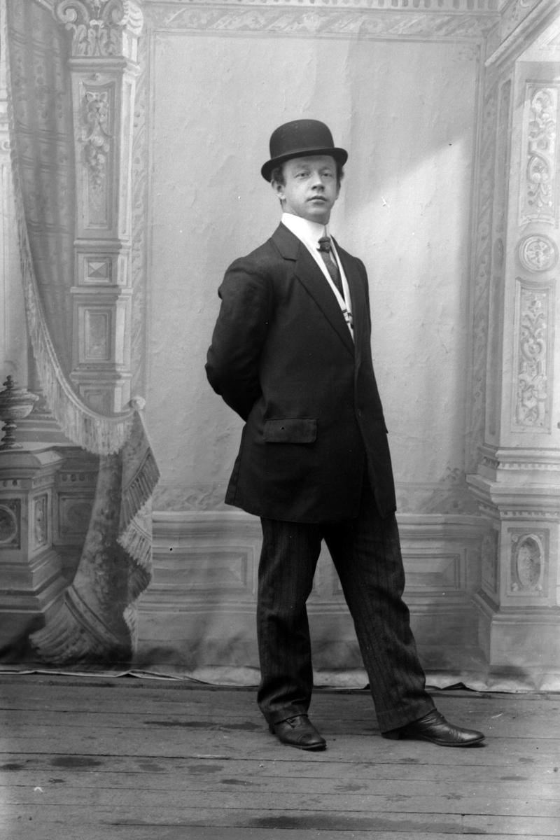 Portrett av en mann i helfigur, fotografert i studio på Andenes.