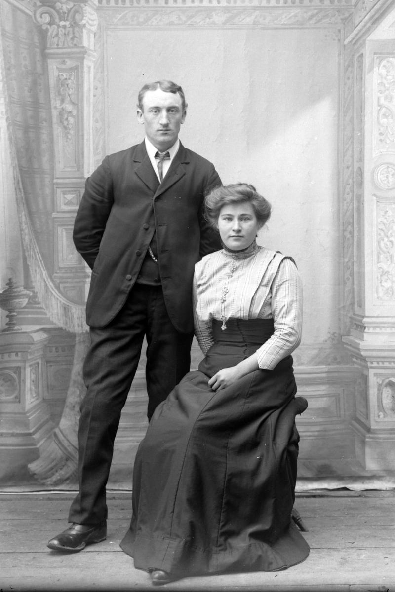 Studioportrett av en sittende kvinne og en stående mann.