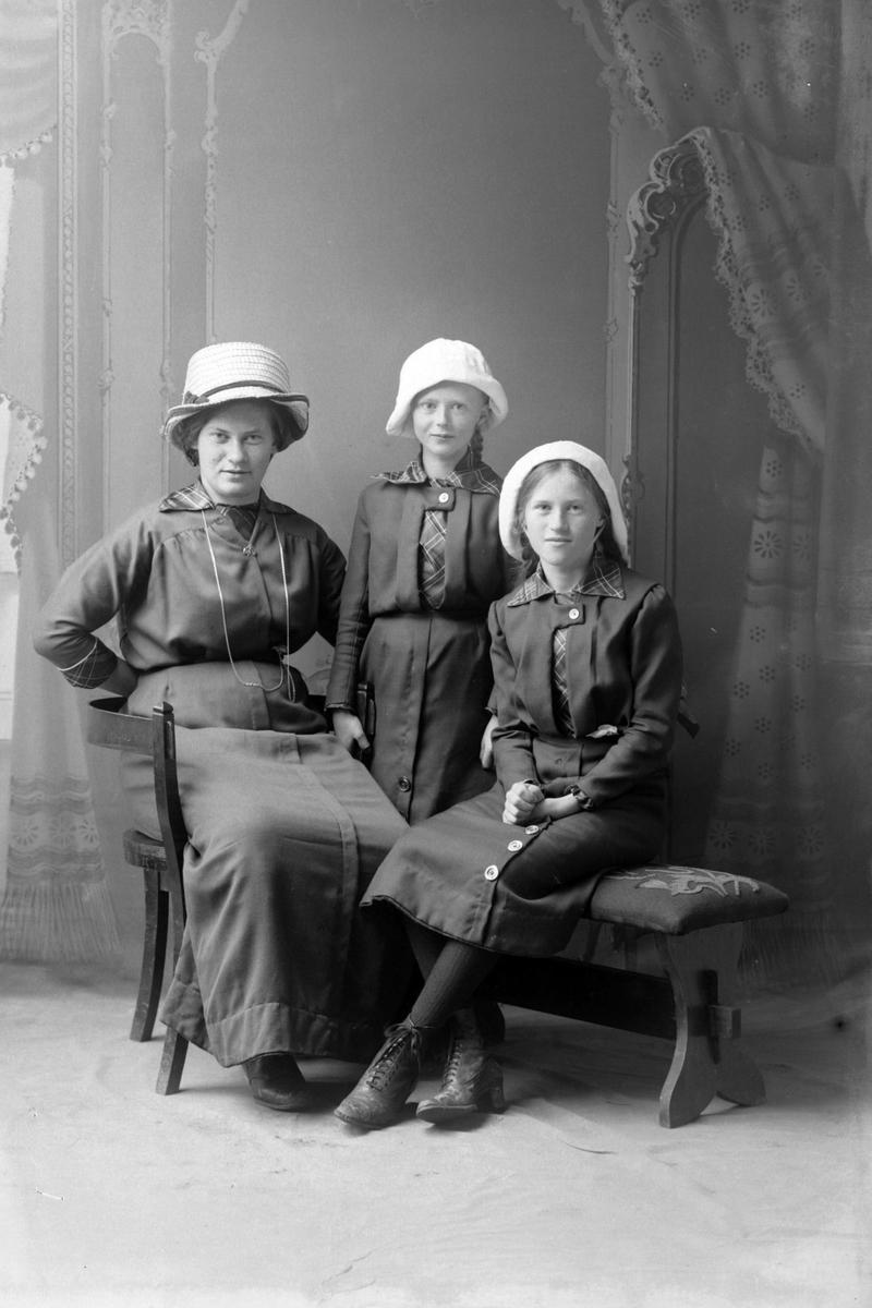 Studioportrett av en kvinne med to jenter, alle med hvite hatter på hodet.