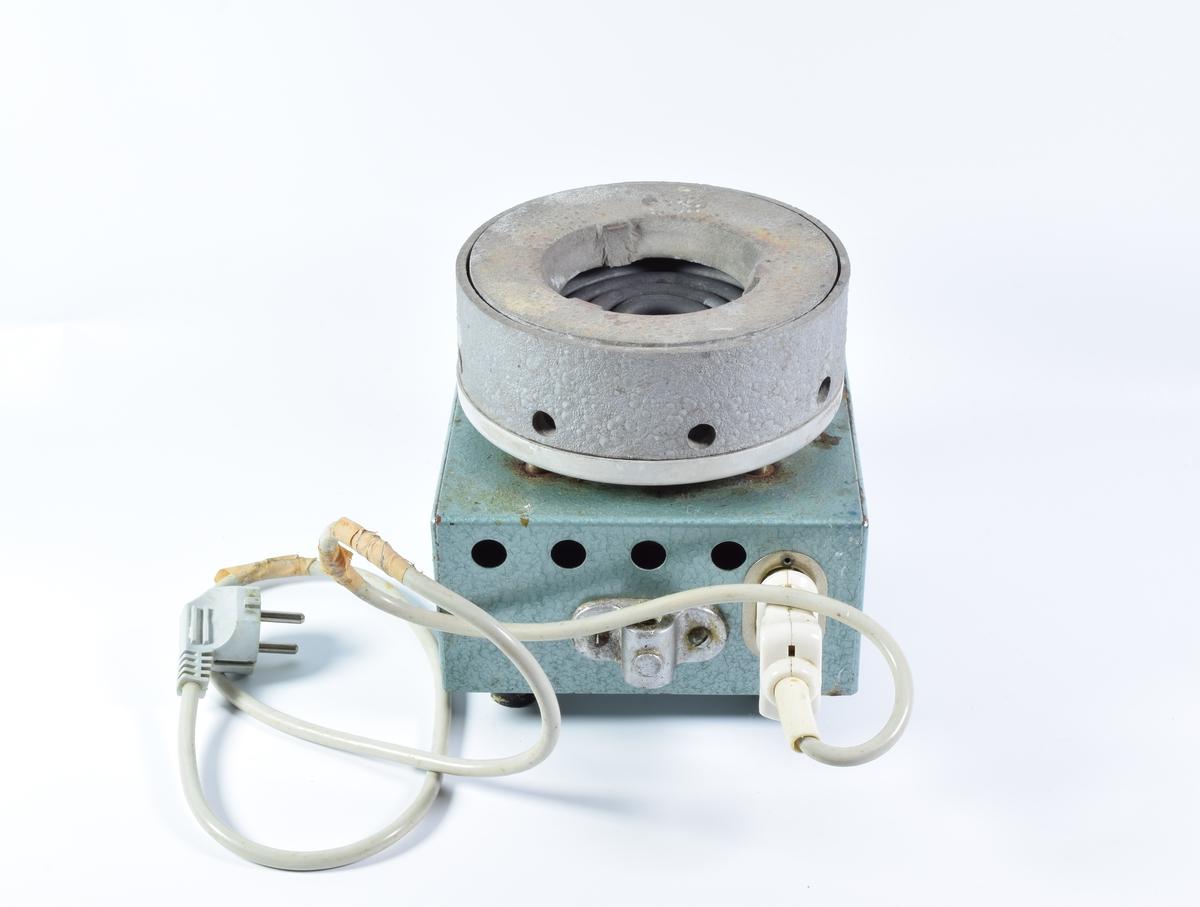 Elektrisk oppvarmingsapparat brukt til varmebad. En kjele plasseres på toppen og apparatet varmes sakte opp. Rommet under kjelen fungerer som varmebad.       Den nederste delen av apparatet er lakkert i lyseblå.