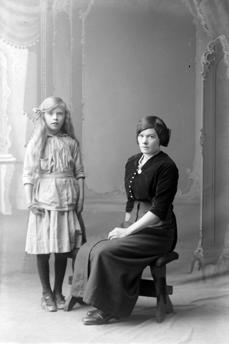 Studioportrett av en ung kvinne ved siden av en jente.