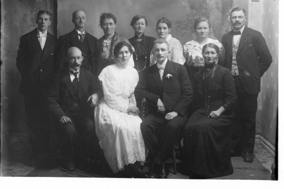 Studioportrett av et brudepar omgitt av en gruppe mennesker, trolig familie.