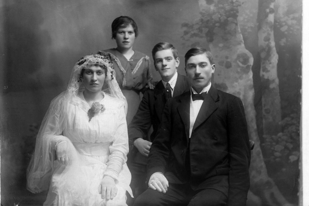 Studioportrett av et brudepar stilt foran en mann og kvinne.