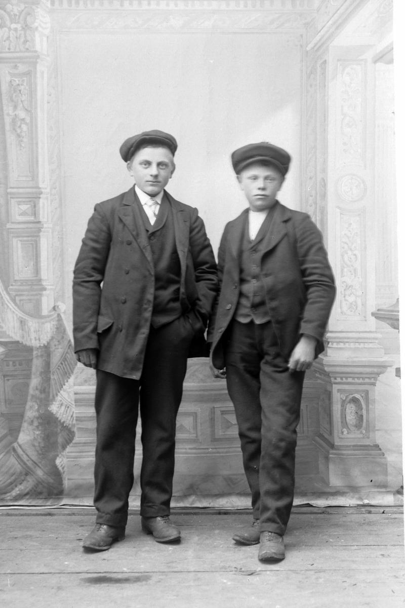 Studioportrett av to gutter med luer.