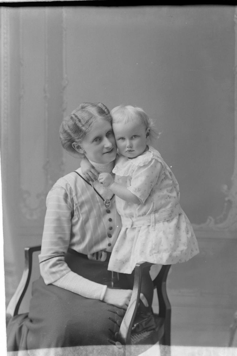Studioportrett av en kvinne som klemmer et barn.