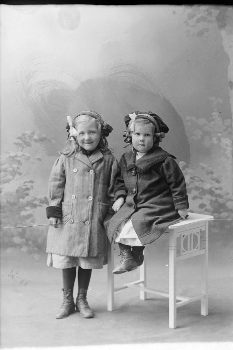 Studioportrett av to jenter i kåper.