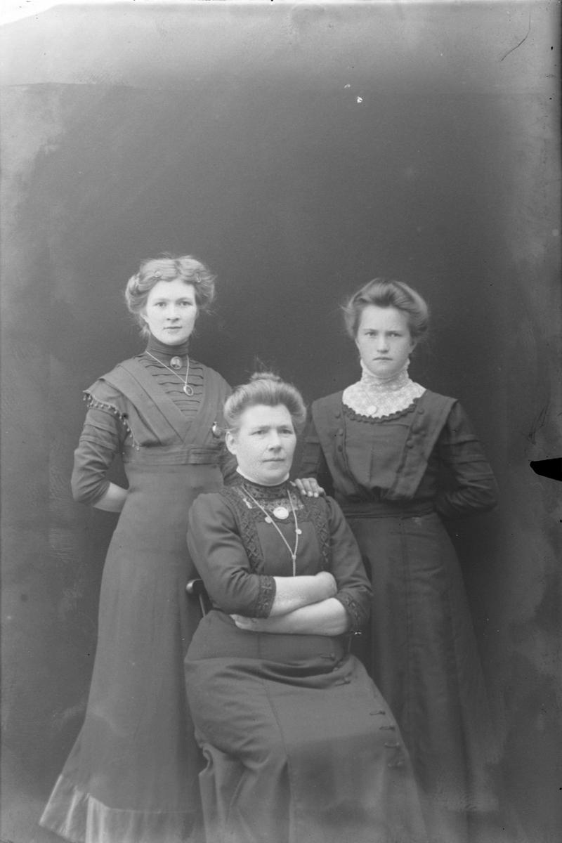 Studioportrett av to kvinner som står bak én som sitter.