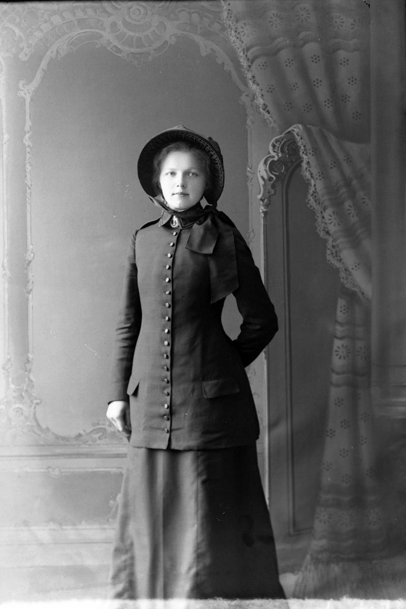Studioportrett av en ung kvinne med jakke og hatt.