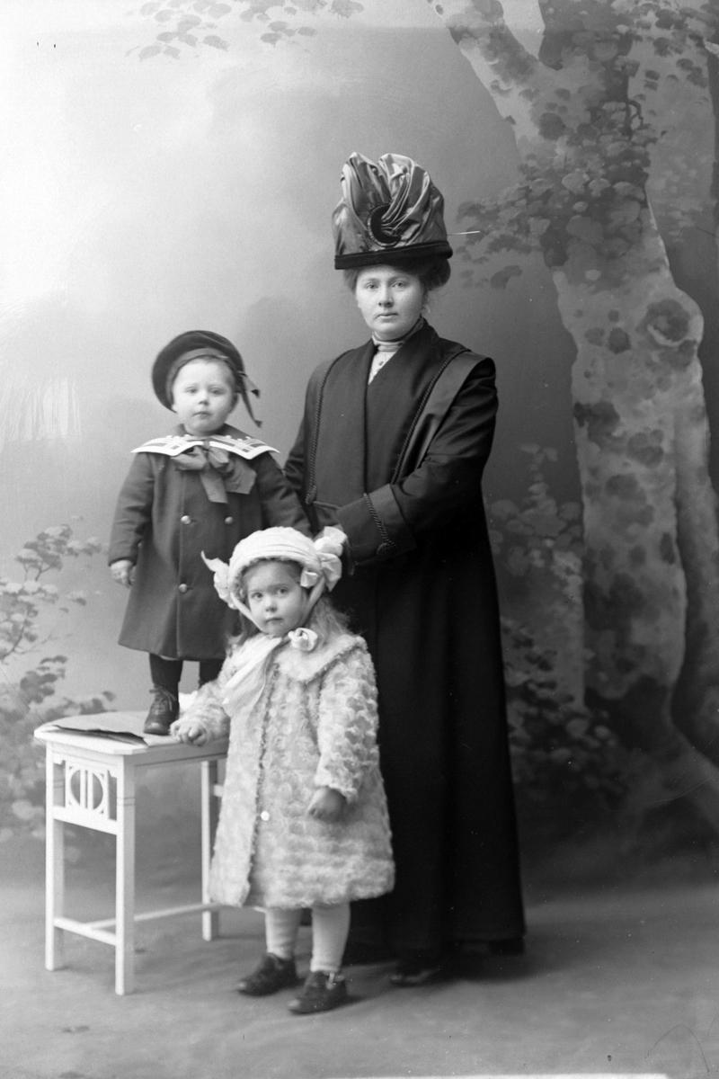 Studioportrett av en kvinne med to barn.