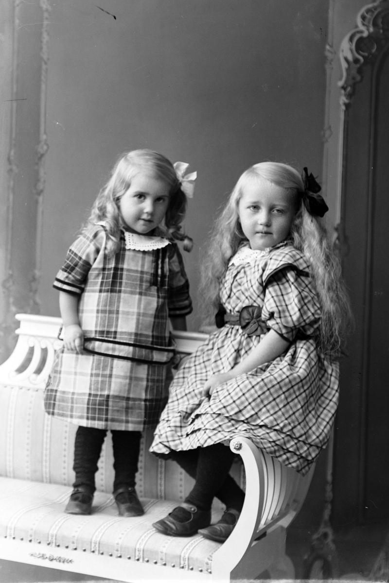 Studioportrett av to jenter på en benk.