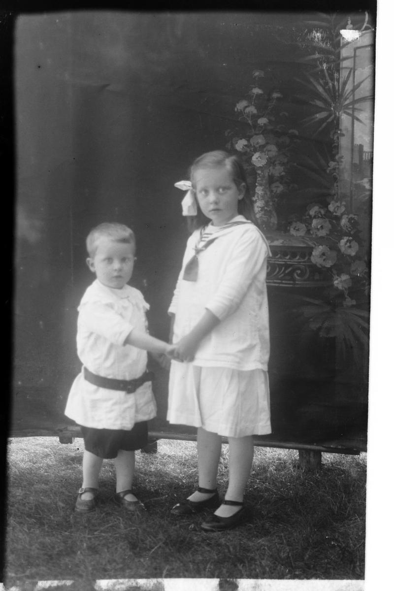 Studioportrett av to barn i lyse klær.