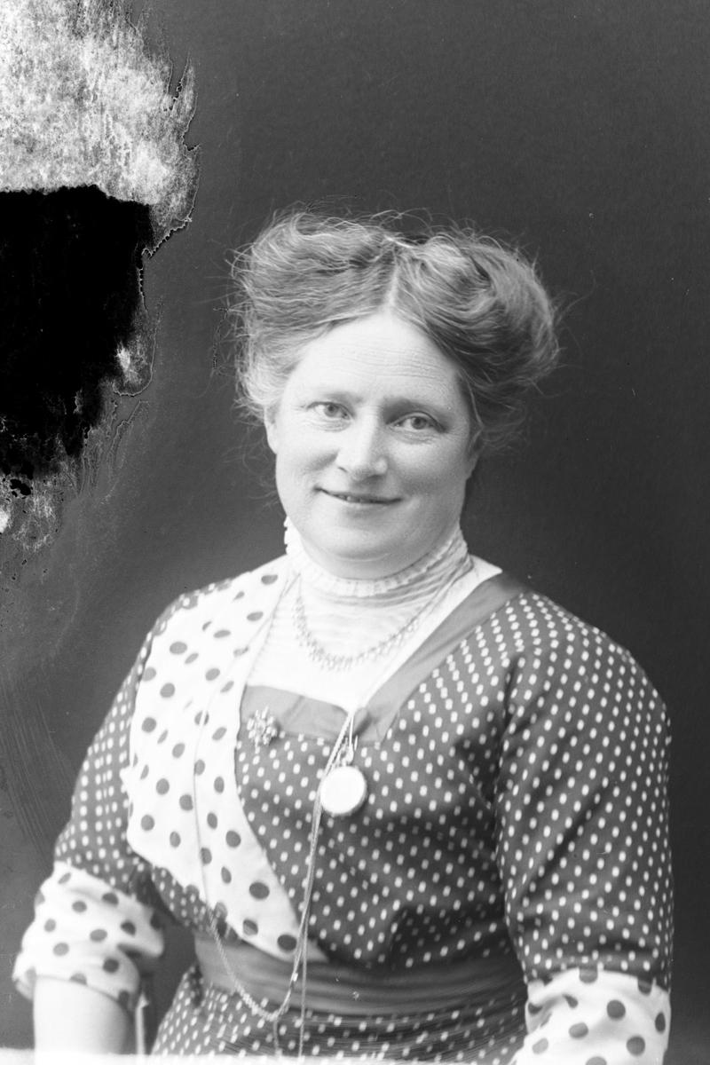 Studioportrett av en kvinne i en prikkete kjole.