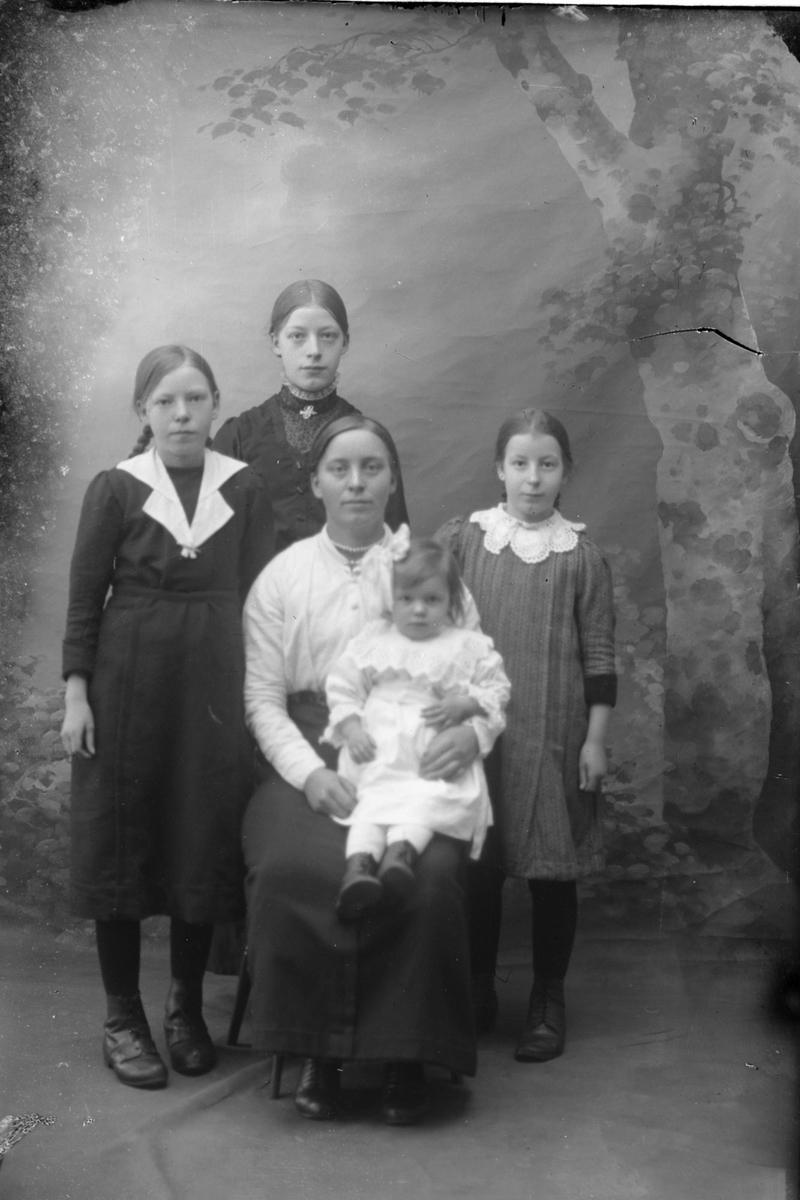Studioportrett av en kvinne omgitt av fire barn.
