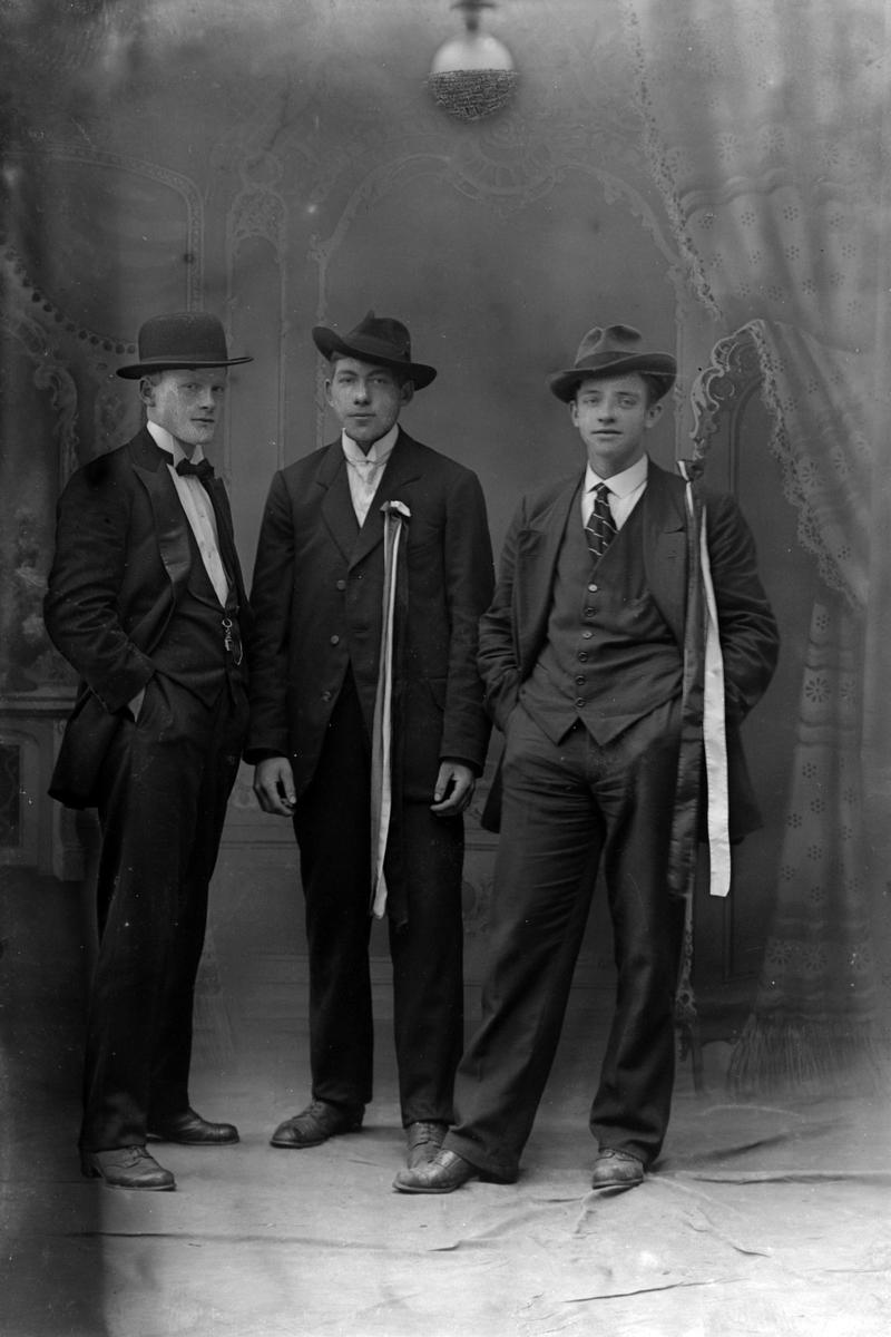Studioportrett av tre menn, to av dem med sløyfer på brystet.