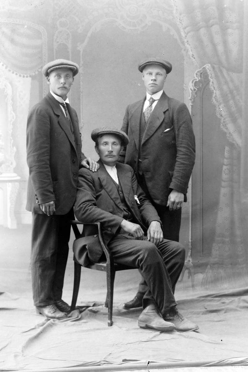Studioportrett av tre menn i helfigur.