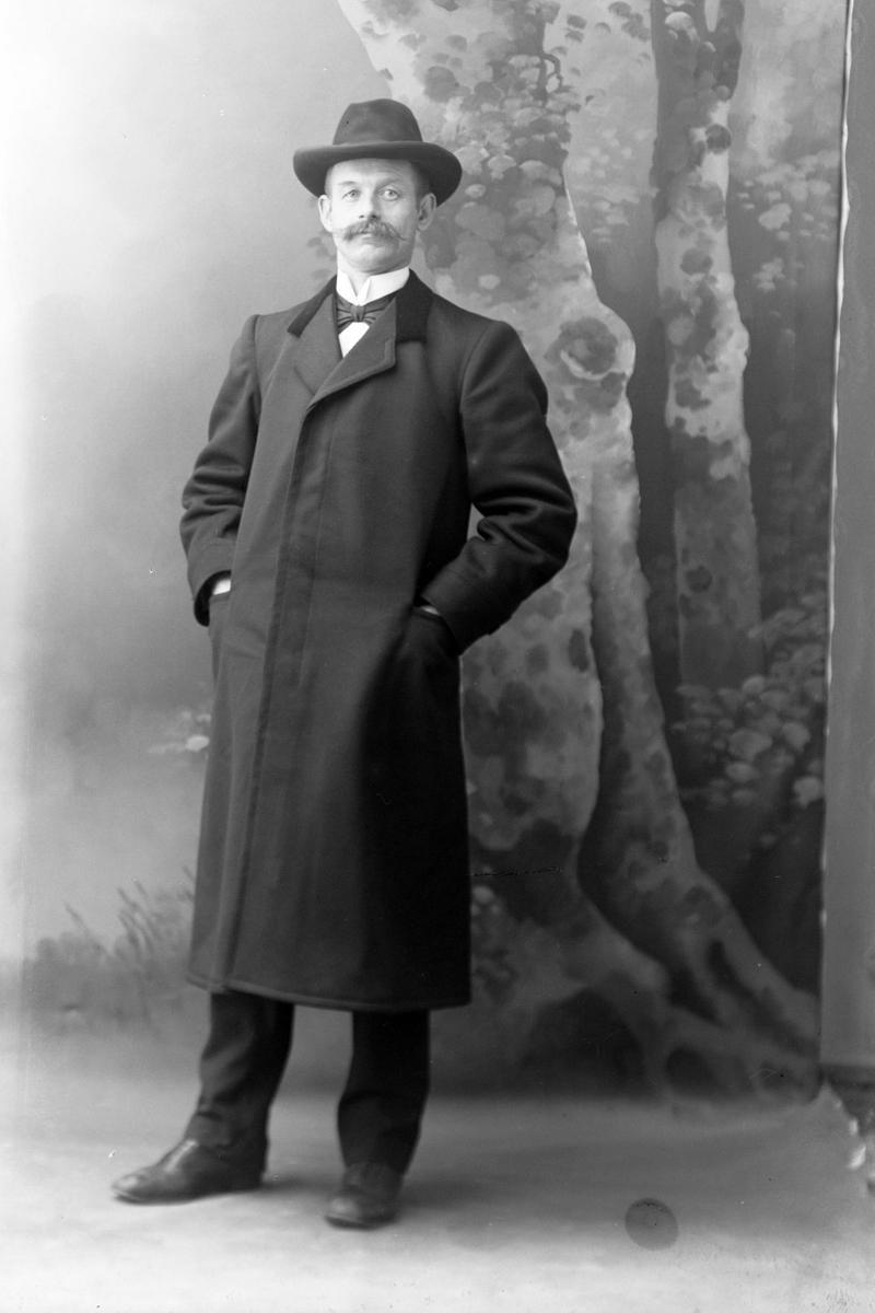 Studioportrett av en mann med hatt og lang frakk.