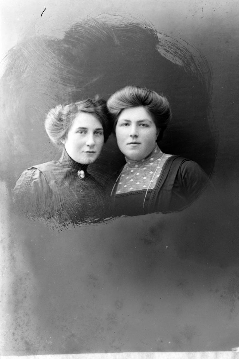 Studioportrett av to kvinner i halvfigur.