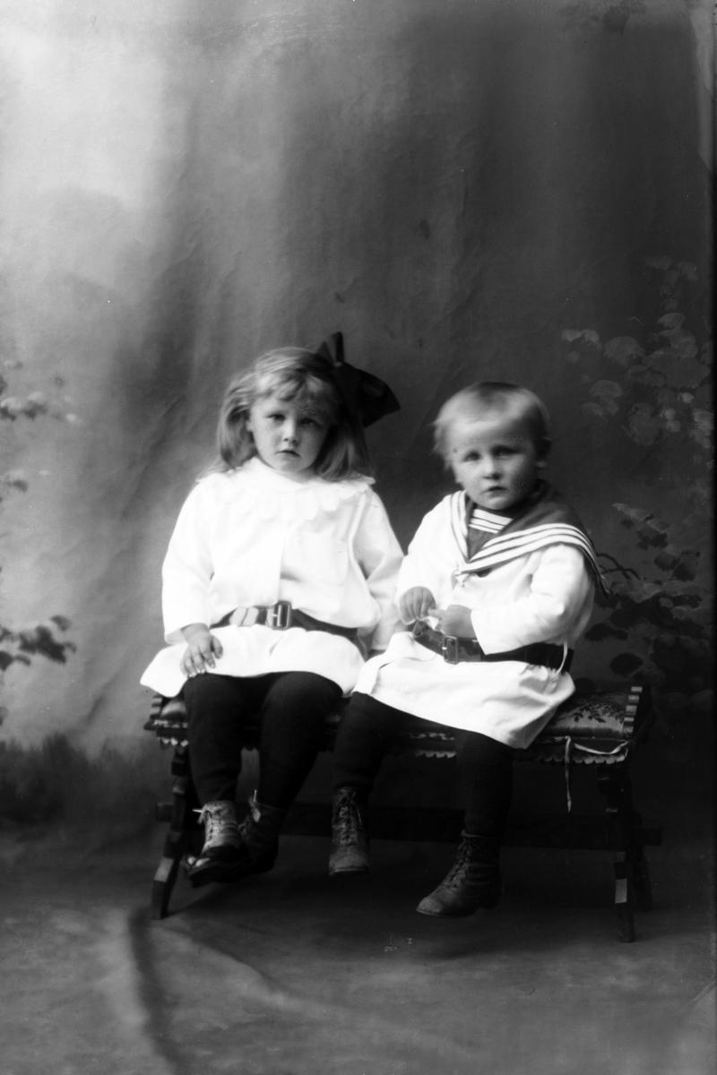 Studioportrett av to barn som sitter.