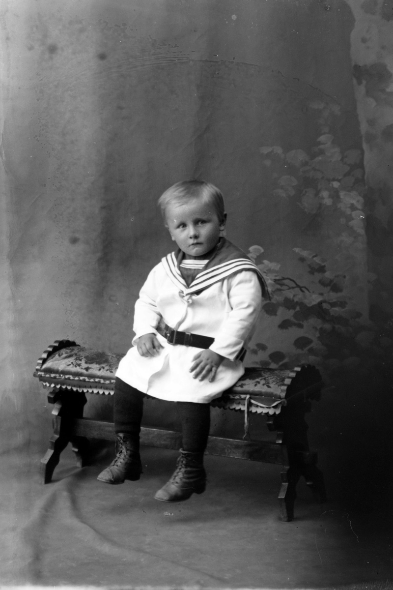 Studioportrett av en gutt som sitter.