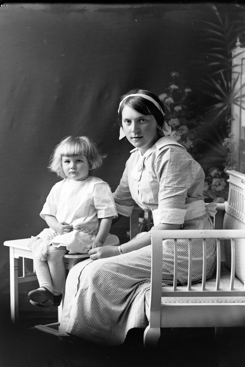 Studioportrett av en kvinne ved et lite barn.