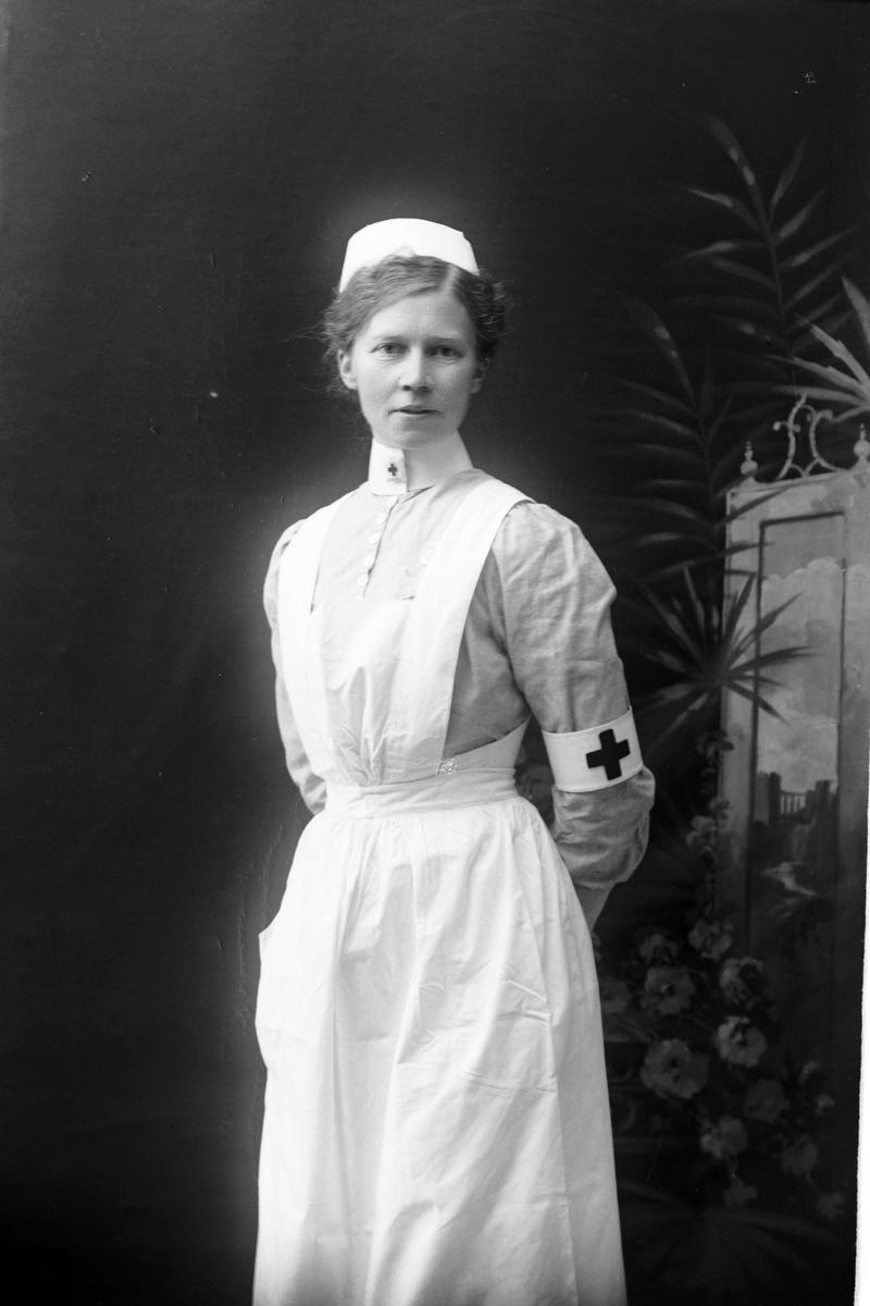 Studioportrett av en sykepleier i uniform.