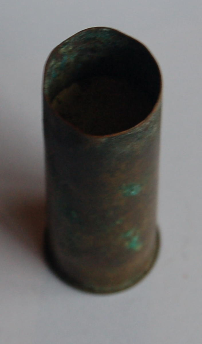 Gjenstanden er ei heimeladda haglpatrone av messing i kaliber 12, og med knallperla intakt.
