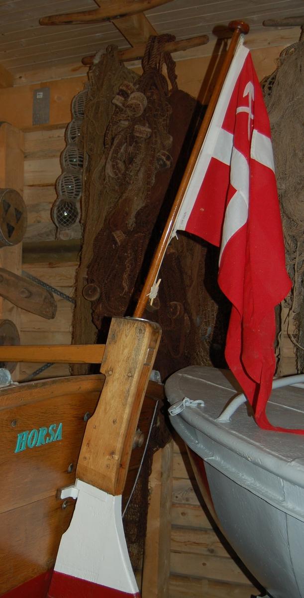 Splittflagg med hvitt kors på sød bunn, med to hvite piler i kryss i øverste rute nermest stanga.