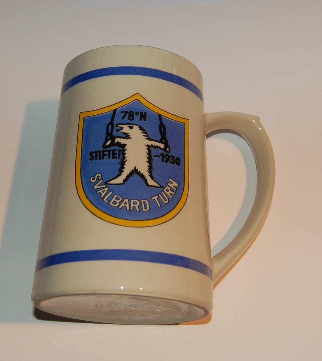 Utsmykka kjegleformet souvenirkrus i glassert porselen. Motiv: Blått emblem med isbjørn i turnringer. Tekst: Svalbard Turn - 78 grader N. Stiftet - 1930.