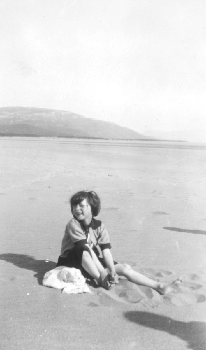 Anna Andersen, også kalt Lille Anna, sitter på stranden i Rustefjelbma. Bildet er tatt sommeren 1930, og sansynligvis i forbindelse med en speiderleir. Fjell ses i bakgrunnen