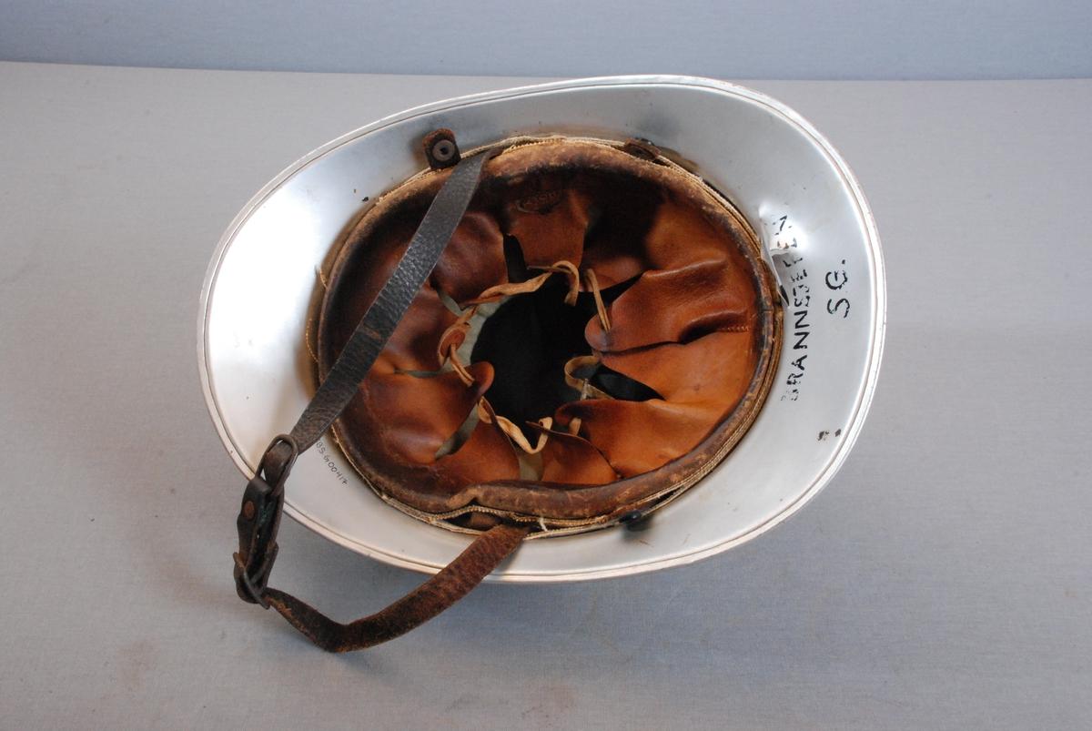 Brannhjelm i metall med hanekam påskrudd på toppen. Hjelmen har sammenhengende brem foran og bak. Innerfor av tekstil. Ytterfor av skinn. Foret kan reguleres med snor. Hakereim i lær. Hemper for feste av nakkeskinn. Hjelmen har Bergen byvåpen emblem med stråler i front. Rundt fronten har hjelmen en metallkrans med bladformede metallløv festet på hjelmens diser. Deksel over festet på ene siden.