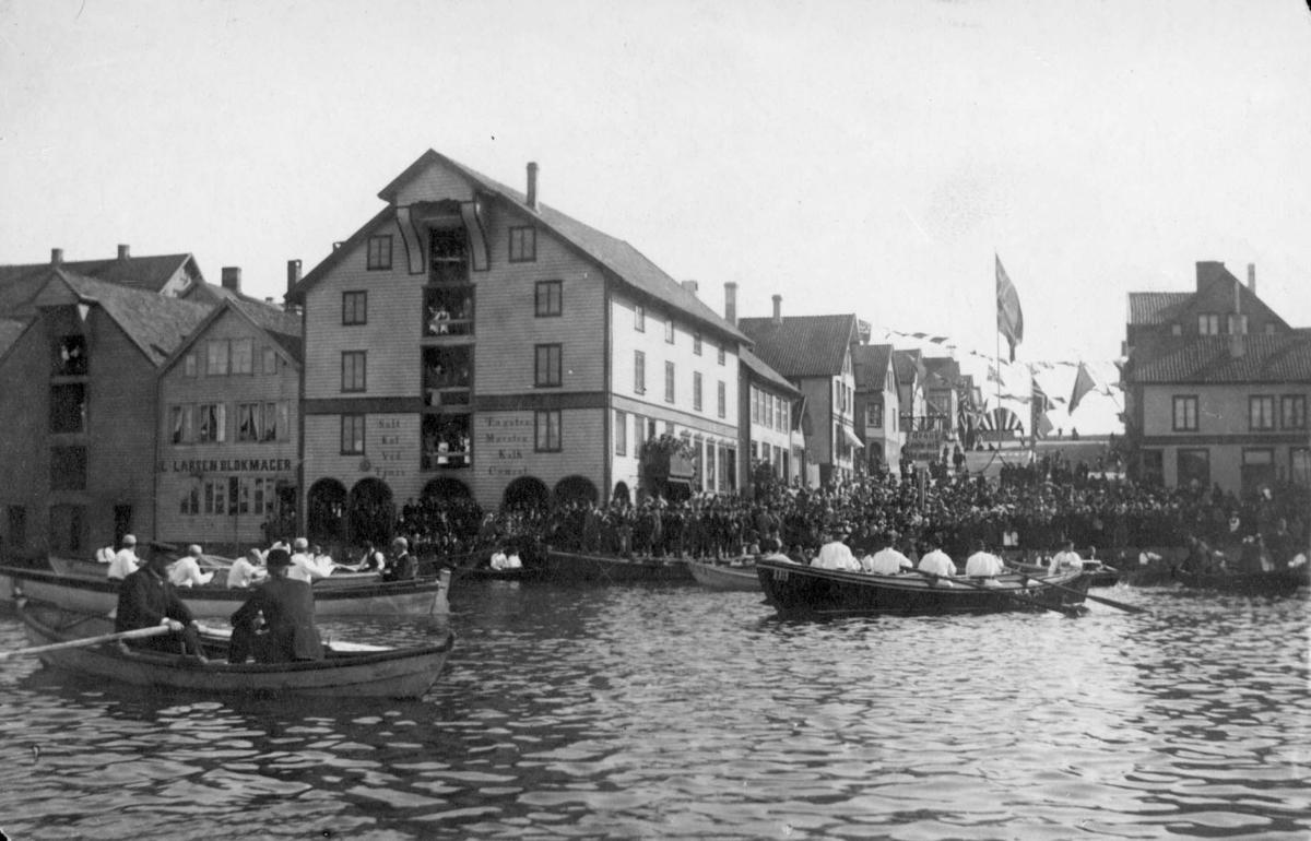 Tadisjonell 17.mai feiring i Torgbakken. Havnebilde med kapproingsbåter i forgrunnen. På kaien festkledde mennesker, enkelte i bunad. I bakgrunnen vaiende flagg og vimpler og oppbygget podium puntet med flagg og maistenger.