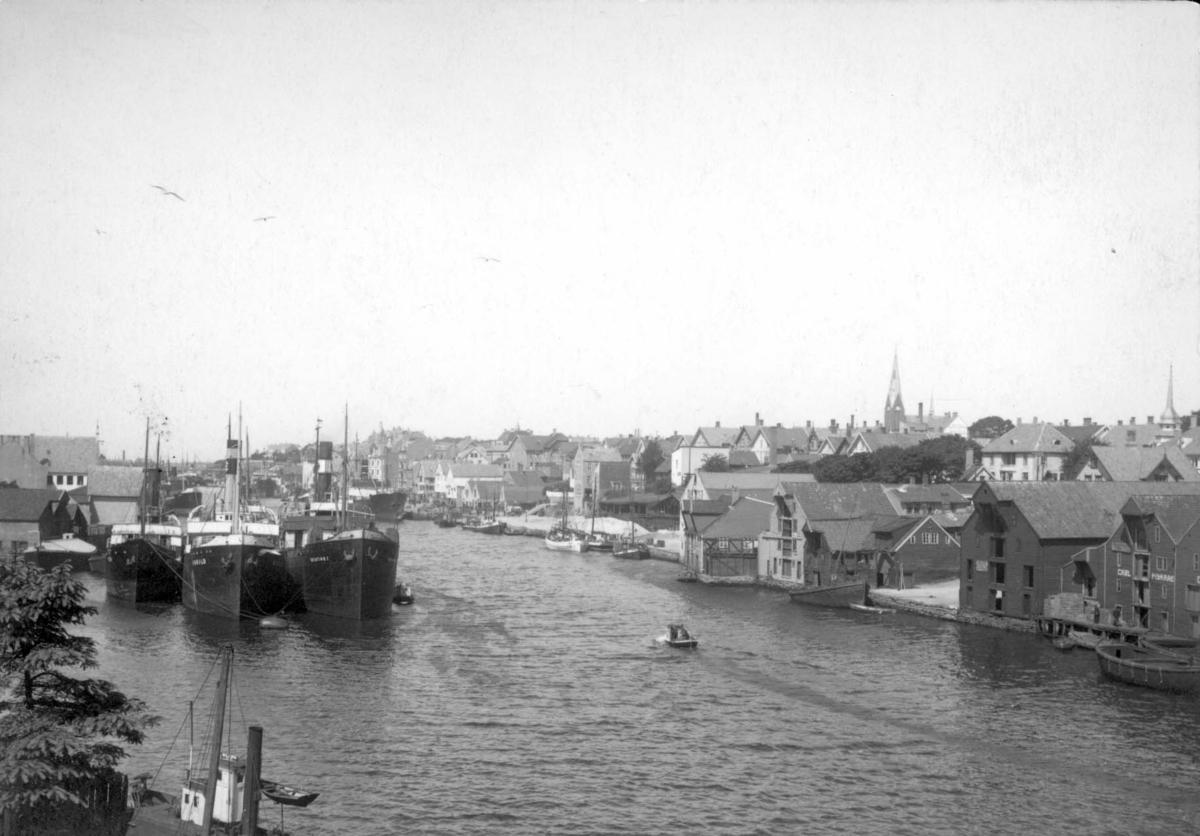 Smedasundet og byen sett fra Kolbeinsens eiendom på Risøy. Til høyre sjøhusene som etterhvert har måtte vike for Saga Maritim. Havnemotiv med dampskip til venstre og byen til høyre i bildet.
