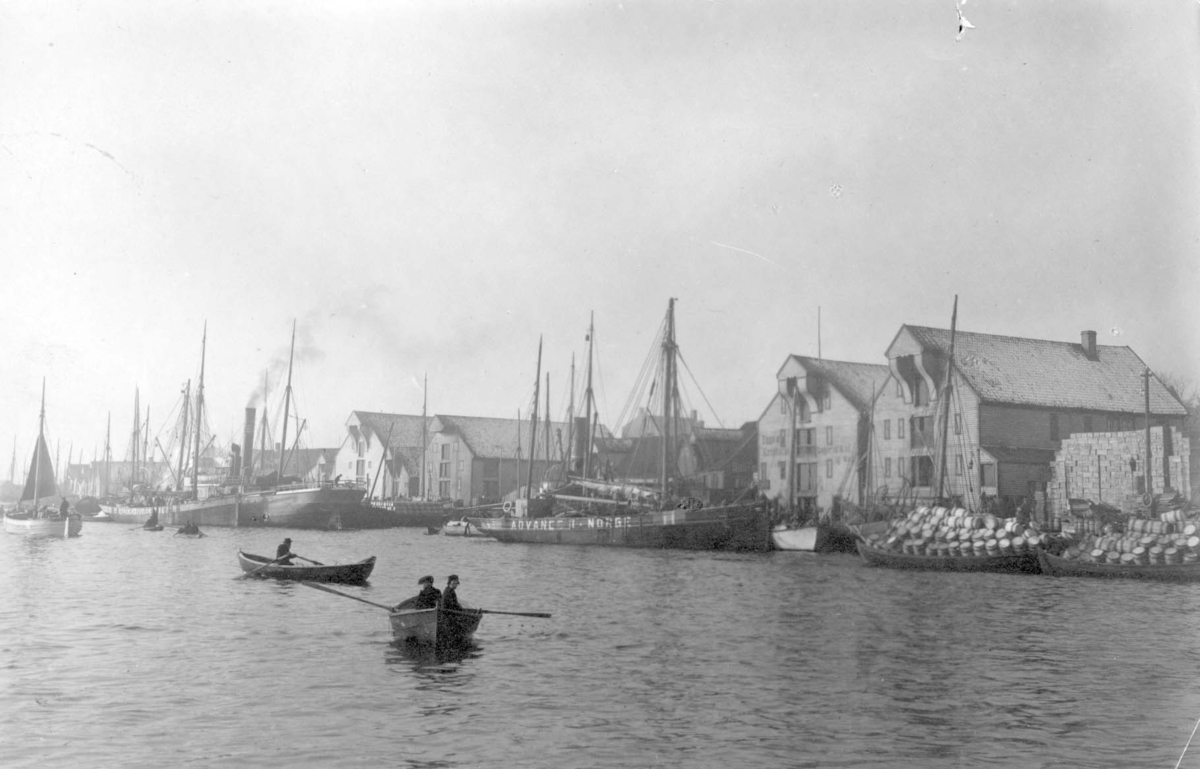 """D/S """"Advance"""" og D/S """"Alice"""" er blant de skipene som ligger ved kai, sannsynligvis ved ballastkaien på Risøy. Utsikt sørvestover. Skipene har påmalt norske flaggfarger. Sjøhus med seil og dampskip foran. Livlig aktivitet med lasting av sildetønner. Robåter ror til og fra."""