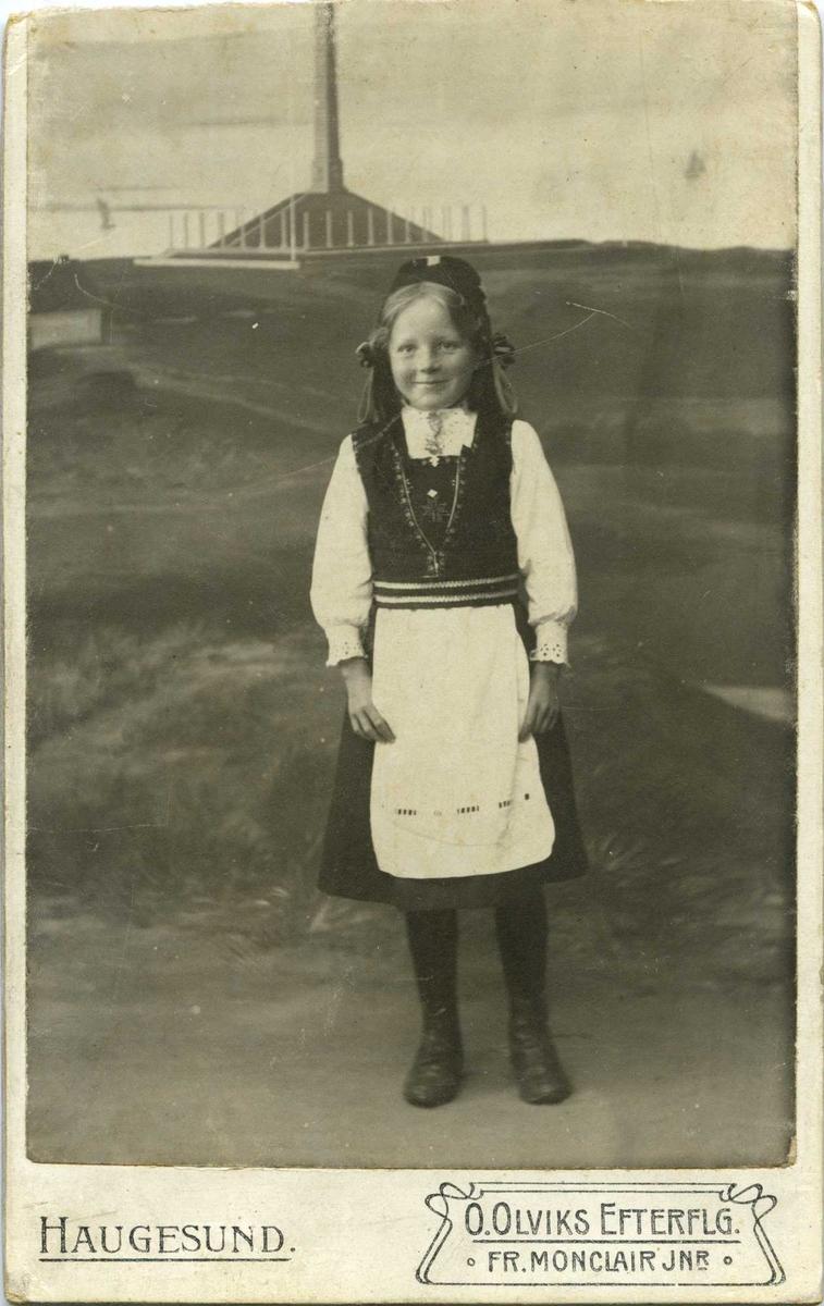 Portrett av jente i Hardanger-drakt. Jenta står foran en kulisse der Haraldstøtta er malt på.