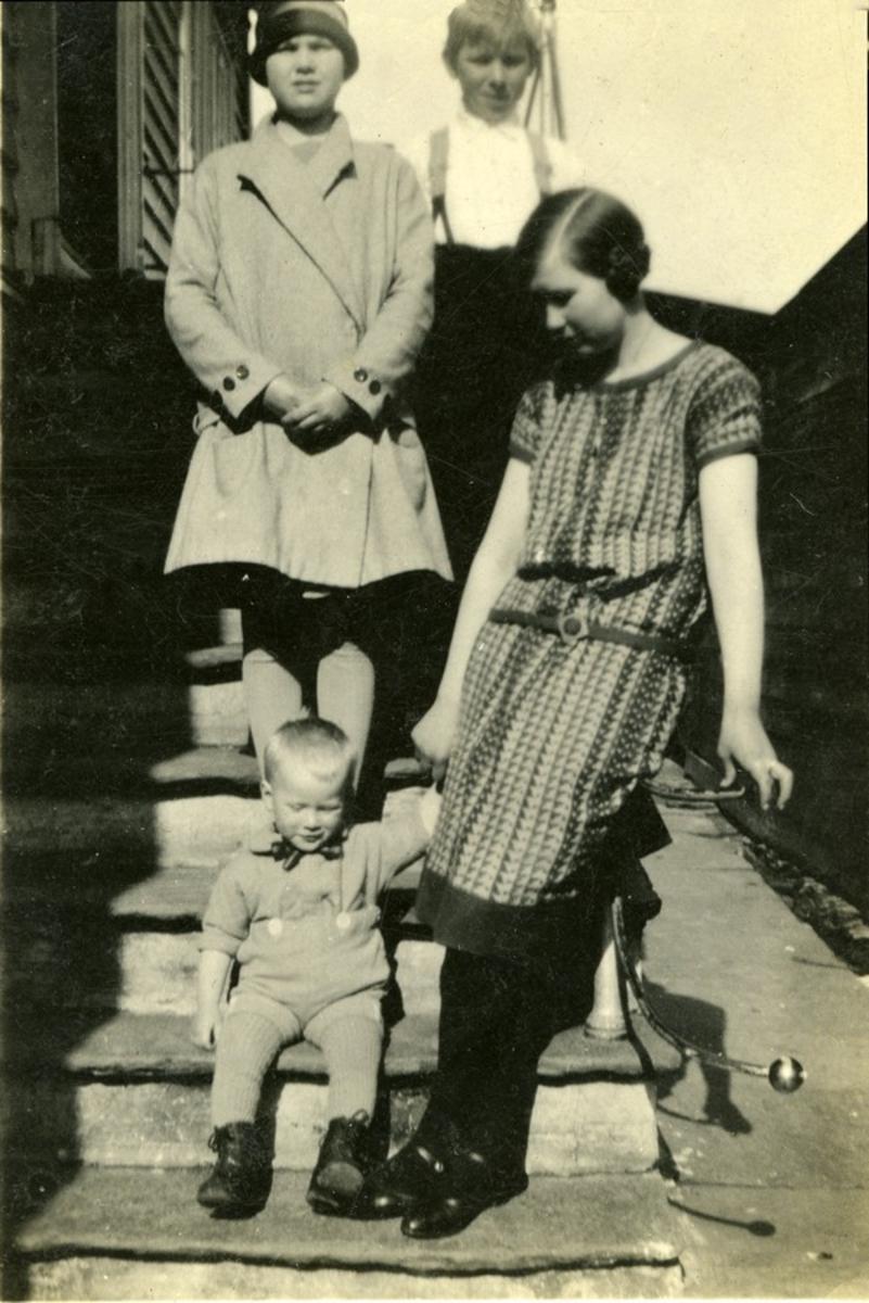 Gruppebilde på trapp. To unge kvinner og to barn