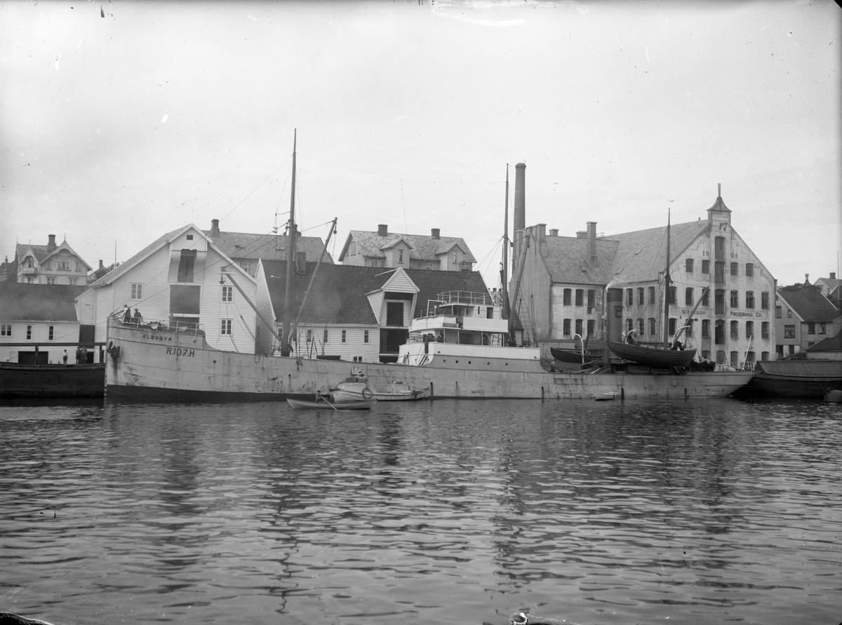 """Damskipet D/S """"Løvøy"""" ved kai i det som antageligvis er Bergen. Bak til høyre ligger industribygget til """"Norwegian Preserving Co.""""."""