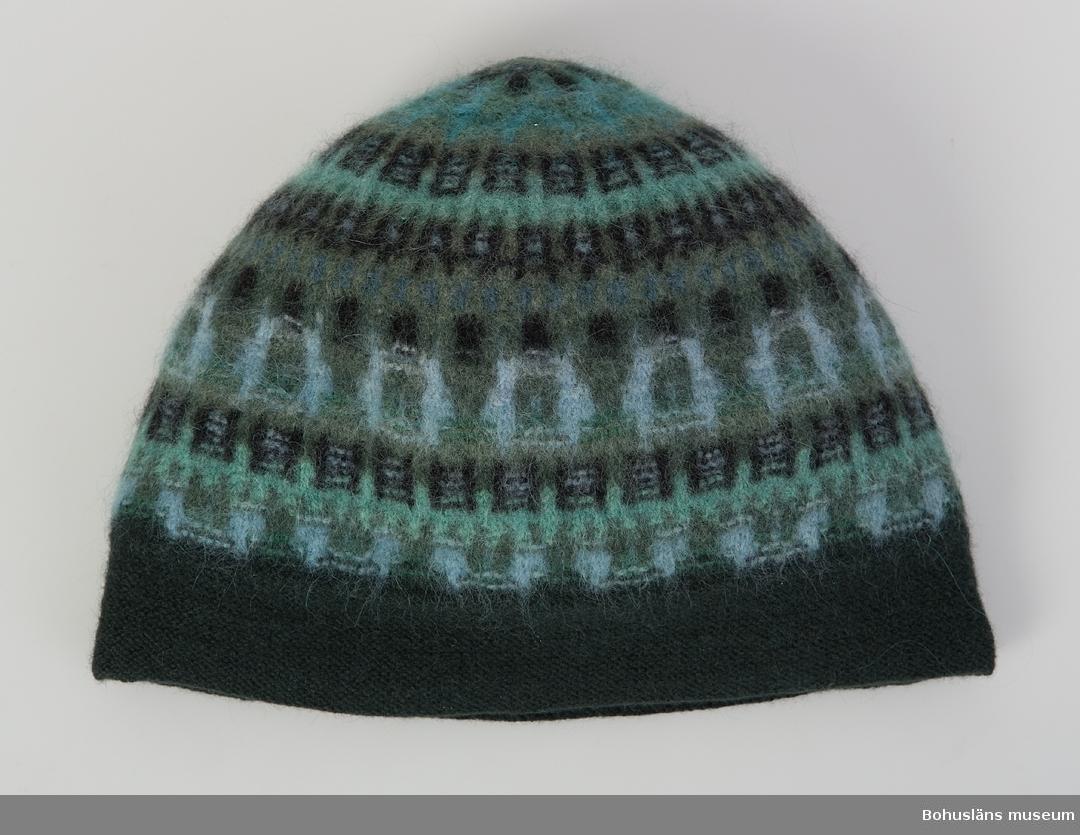 Mössa i sotarmodell i mönstret Skogsmörkret med åtta olika nyanser av grönt, blått och svart med original-etikett, nederkanten stickad i aviga. Välbevarad. Modell av Annika Malmström-Bladini från 1953.  Givaren har fått mössan som gåva på 1970-talet av en god vän men vet ej var den är inköpt. Den är använd tillsammans med koftan, UM027884.  Plaggen visades i en egenproducerad  mindre utställning om Bohus Stickning på Bohusläns museum 2004.  Se Bilagepärmen UM027884 för artikel ur tidningen Form, nr. 7 1954 där Annika Malmström och bl. a. Skogsmörkret presenteras.  För ytterligare uppgifter om givaren, se UM27884.