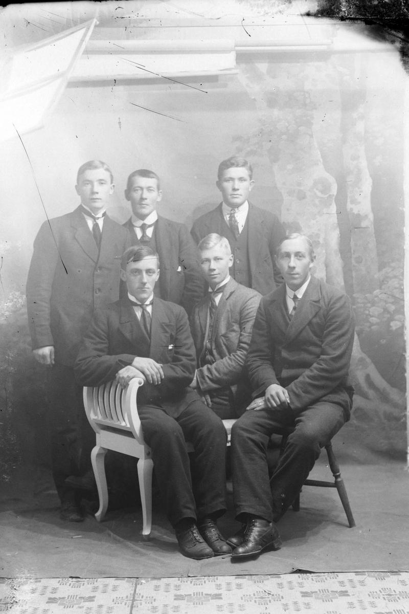Studioportrett av seks menn i helfigur.