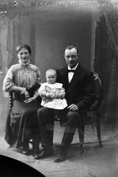 Studioportrett av en mann og kvinne med et barn.