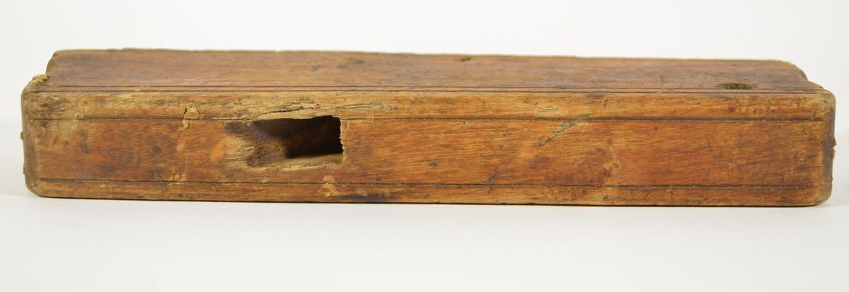 Rektangulær trekloss med en hevet kant langs den underste langsiden, etterfulgt av en konkav rille i samme side. Skråstilt gjennomgående firkantet hull med en liten avrundet uthuling til å plassere blad og kile. Et hull er drillet gjennom hele klossens bredde på den ene siden.   Smal høvel til å høvle spor eller kant i listverk. Høvelen mangler blad.