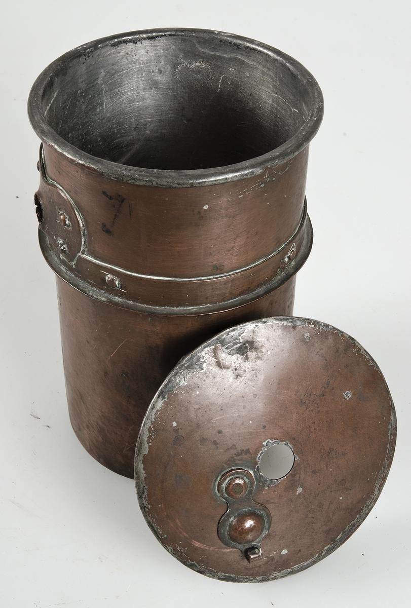 Kastrull av koppar, handtag av svarvat trä med spår av svart färg. På locket ett hål med en vridbar kupa.