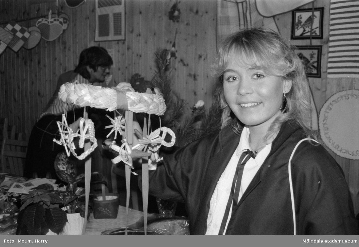"""Julbasar i Kållereds Missionskyrka, år 1984. """"Annika Larsson hittade en vacker halmdekoration på basaren.""""  För mer information om bilden se under tilläggsinformation."""