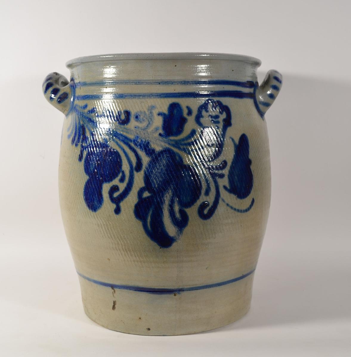 Grå krukke i lett konveks form i leirgods med blå dekor. To håndtak ved krukkens åpning.