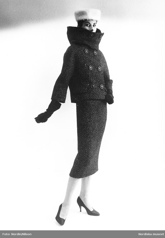 Modell i dräkt med hög krage, handskar, pumps och vit pälshatt. Original från Givenchy.